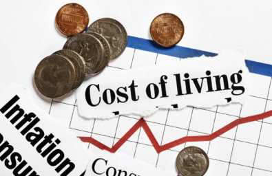 Coins rest on rising graph and cost of living headlines
